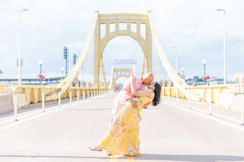 groom dipping his bride in the center of the Roberto Clemente Bridge
