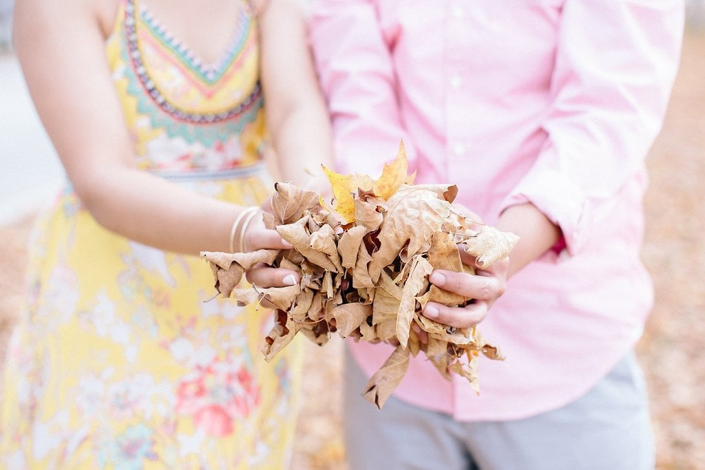 Bride and groom holding leaves in their hands