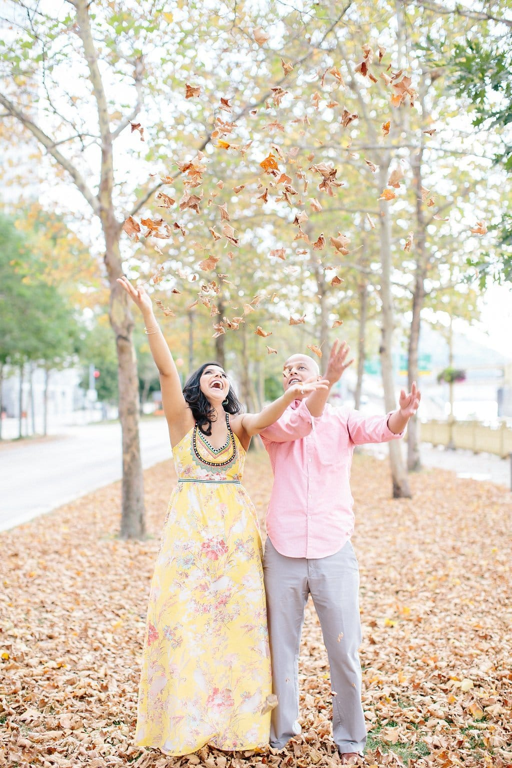 Bride and groom dancing and throwing leaves during engagement Session