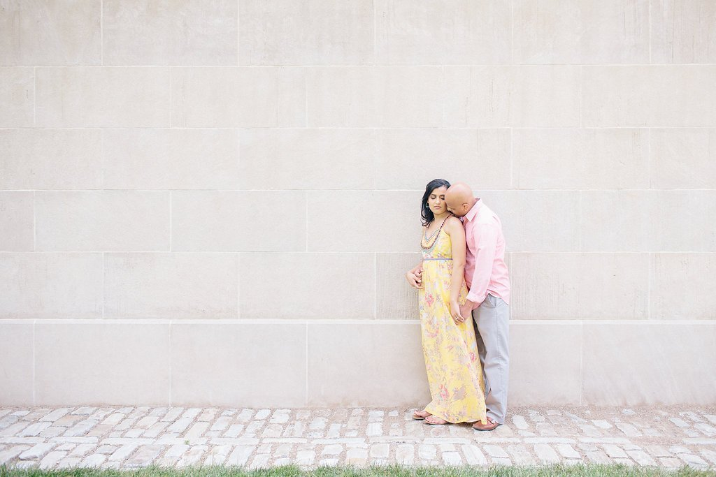 Bride and groom posing against and white stone wall