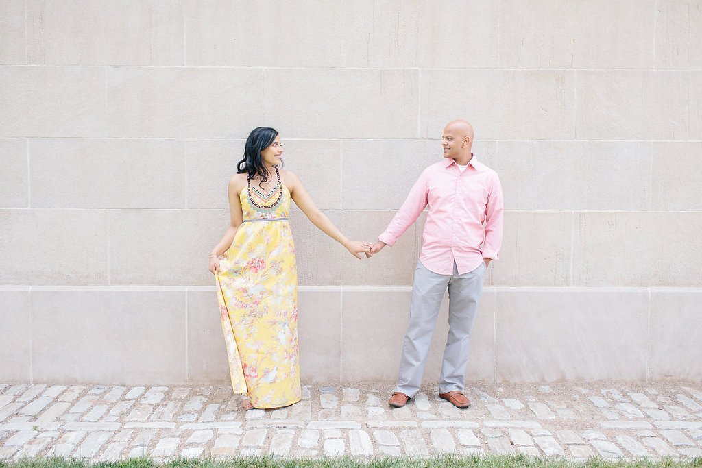 couple holding hands for portraits in front of a white stone wall at the point