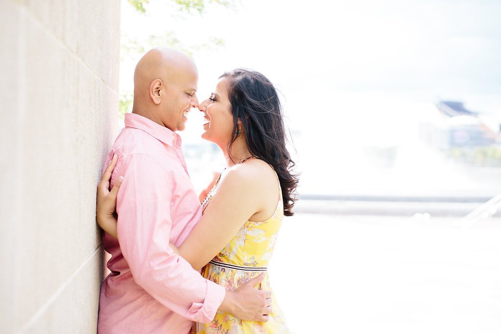 Couple kissing against a white stone wall near the point fountain