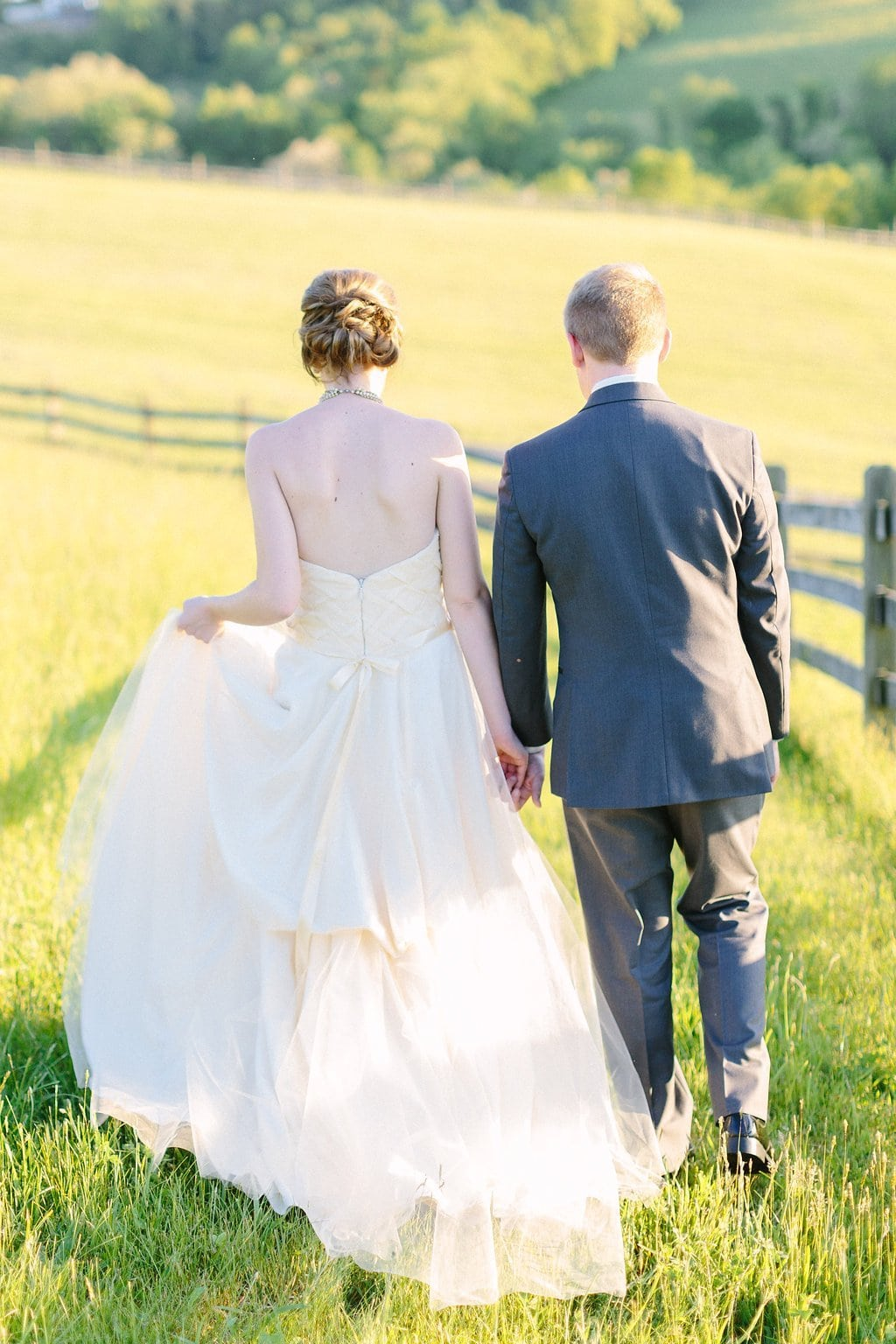 bride and groom walking through a field on the farm