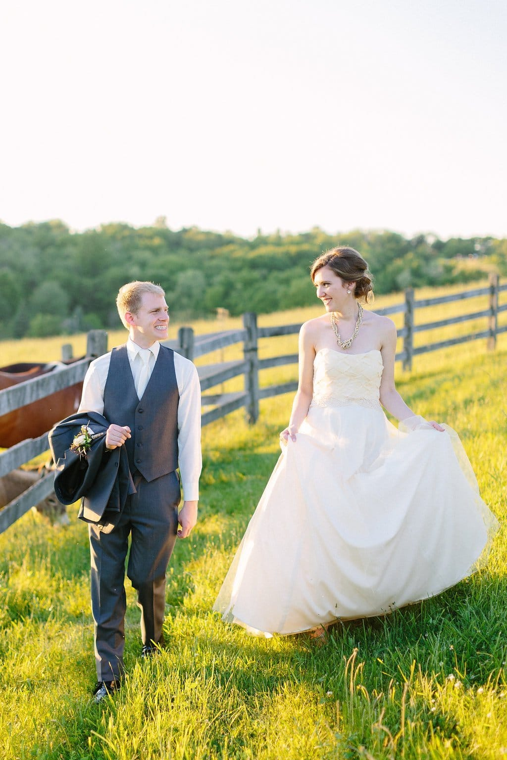 Bride and groom walking through a field with a farm horse