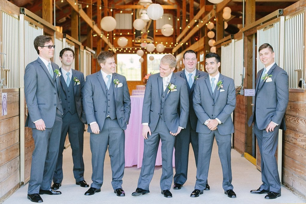groom and groomsmen hanging out in the horse stables