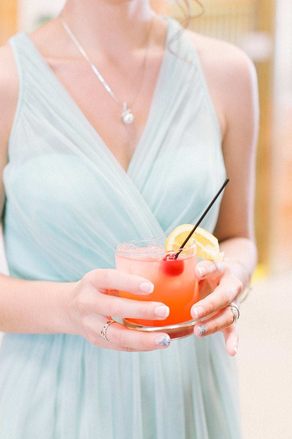 bridesmaid holding signature cocktail at cocktail hour