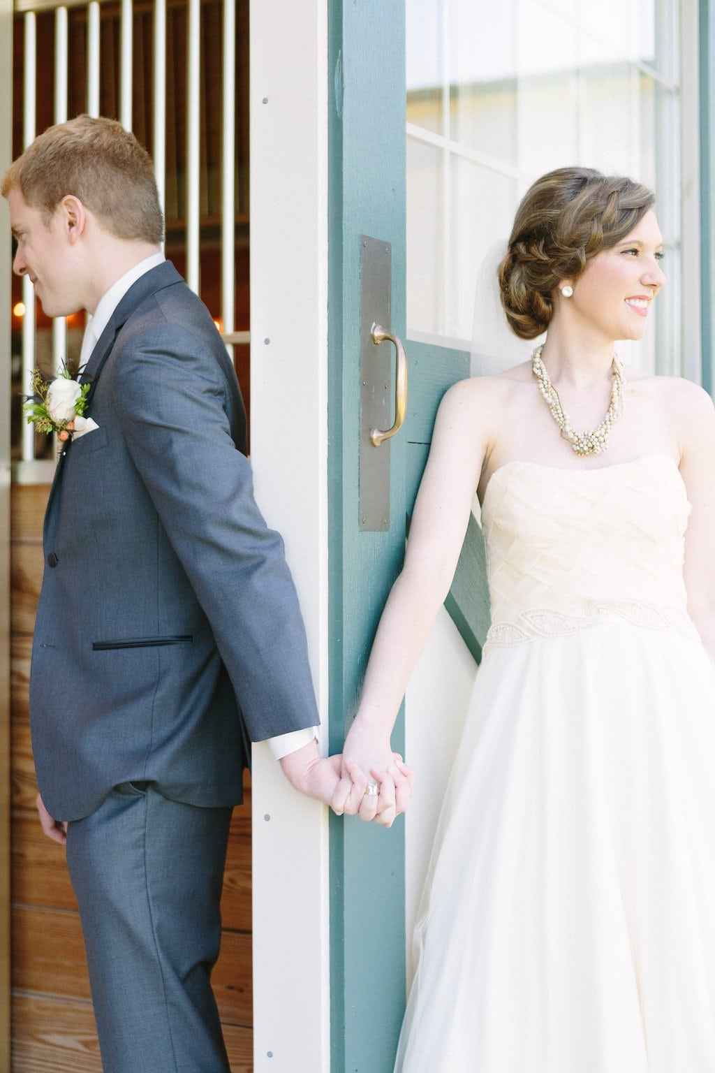bride and groom share a moment holding hands before seeing each other
