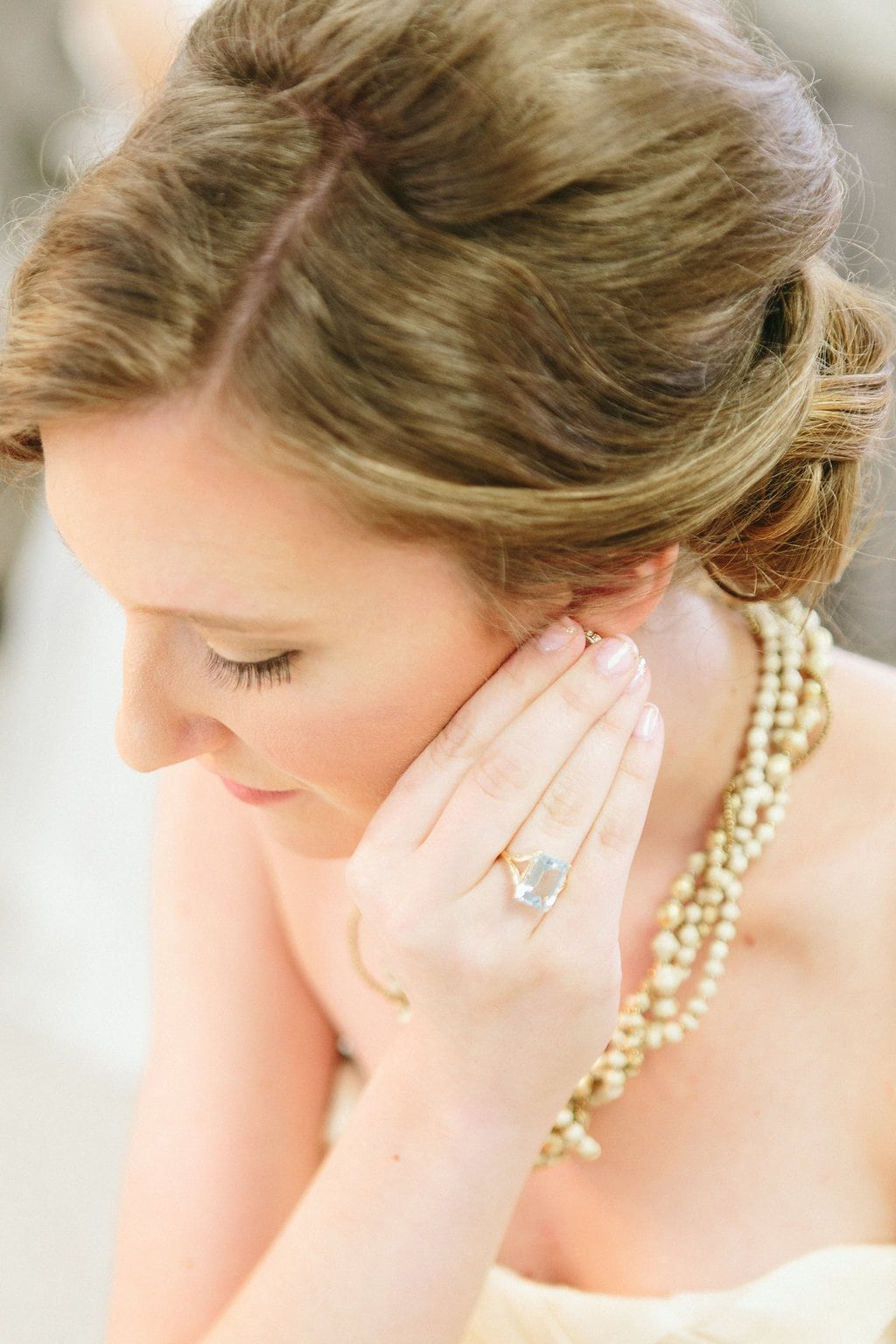 bride putting on earrings and jewelry