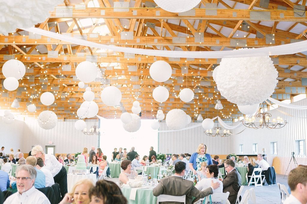 Wedding reception with white paper lanterns and pale green linens