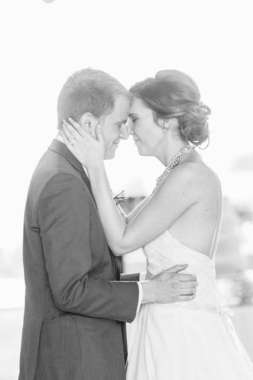 Bride and groom embracing during first dance in black and white