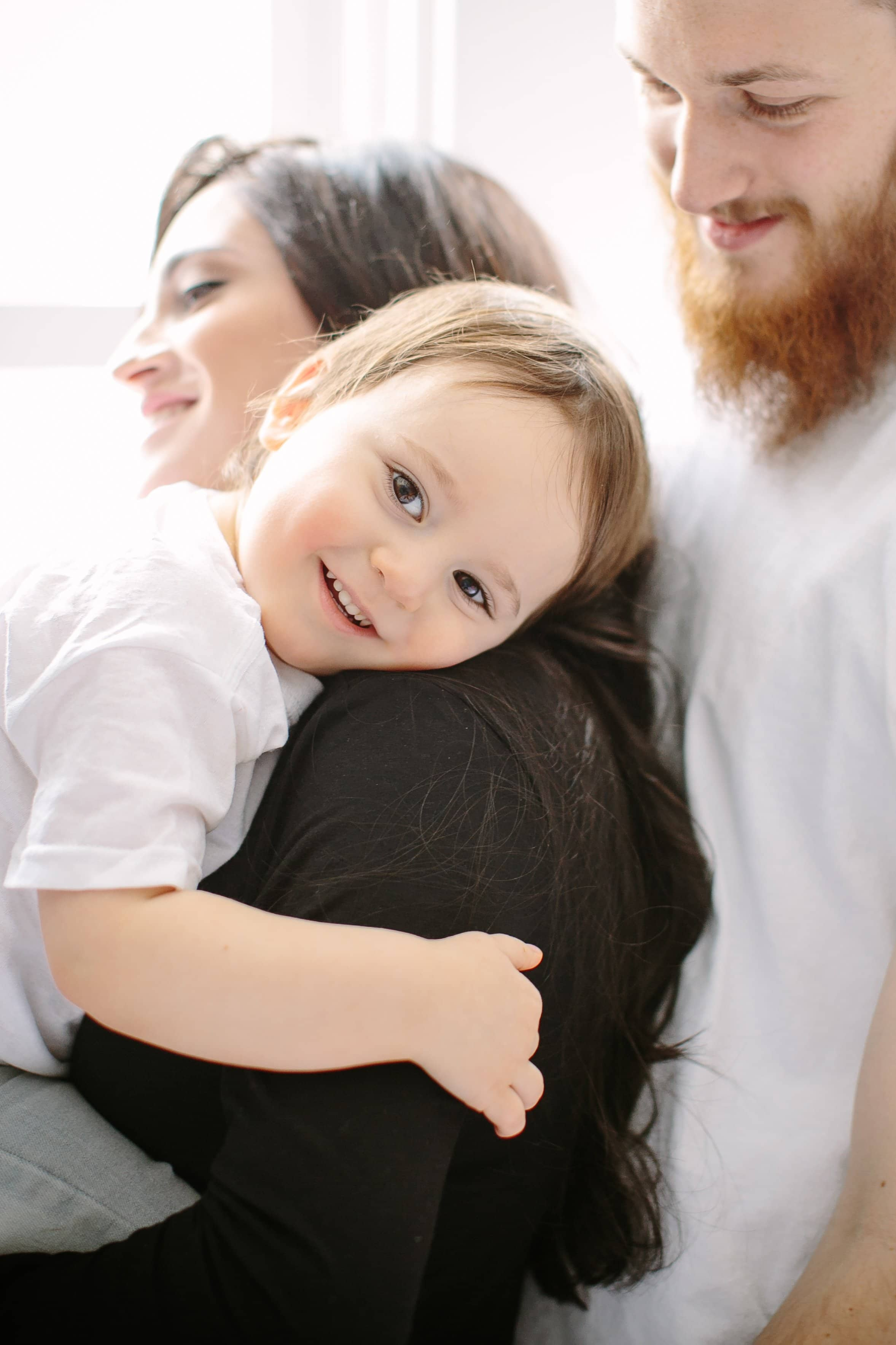 toddler being embraced by parents during photo session
