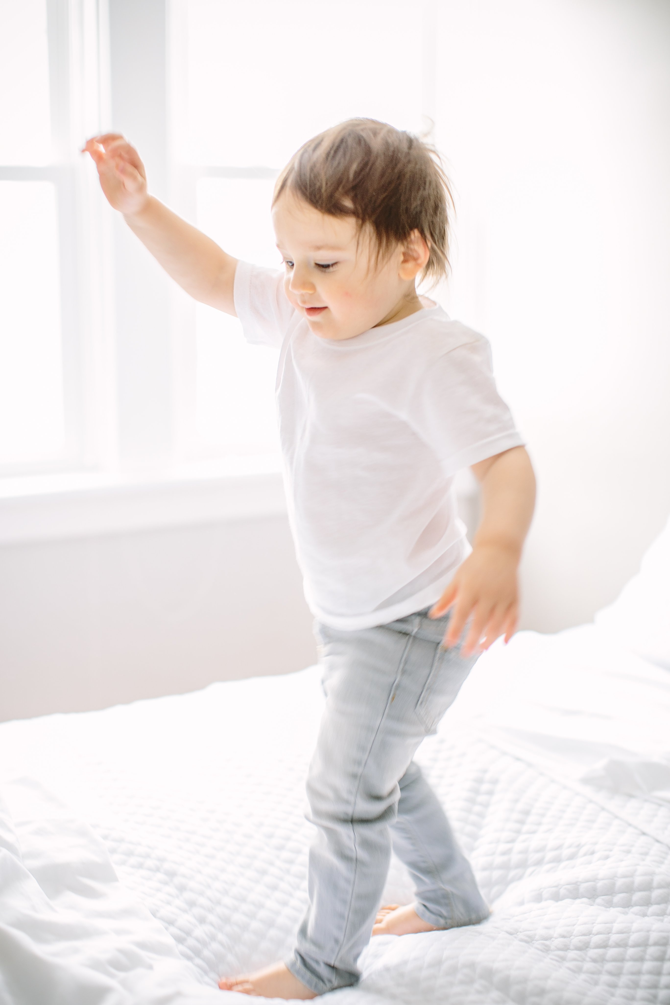 toddler jumping on bed with white sheets