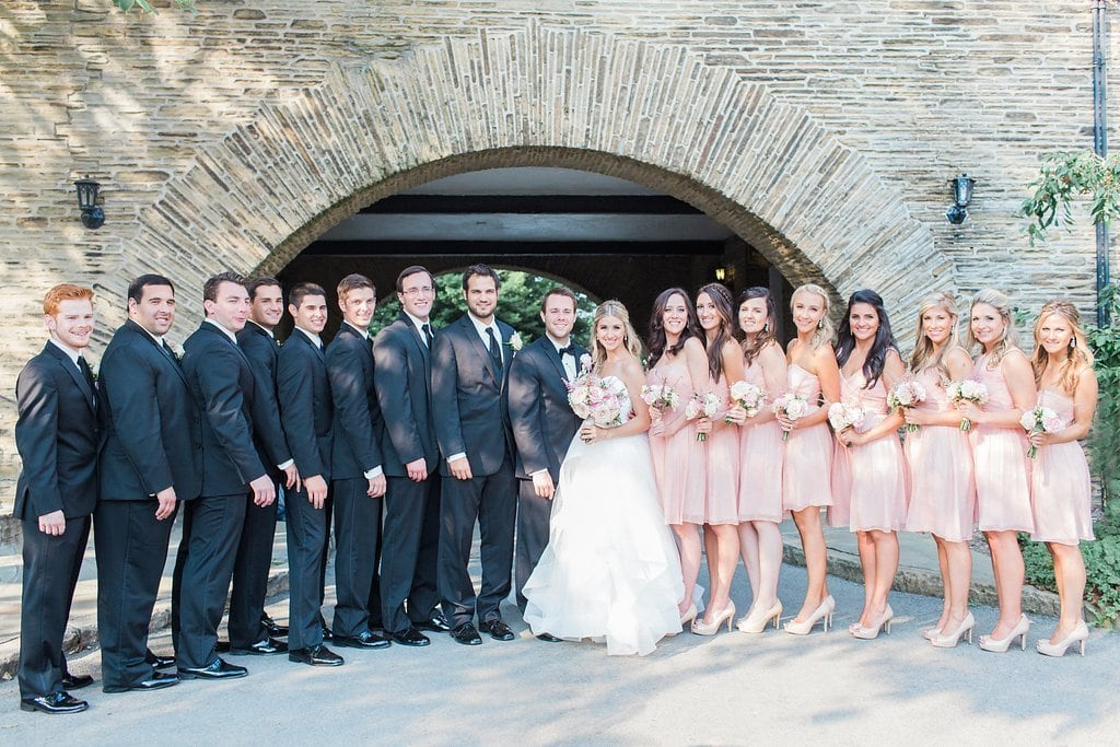 entire bridal party standing under the archway at Longue Vue Club