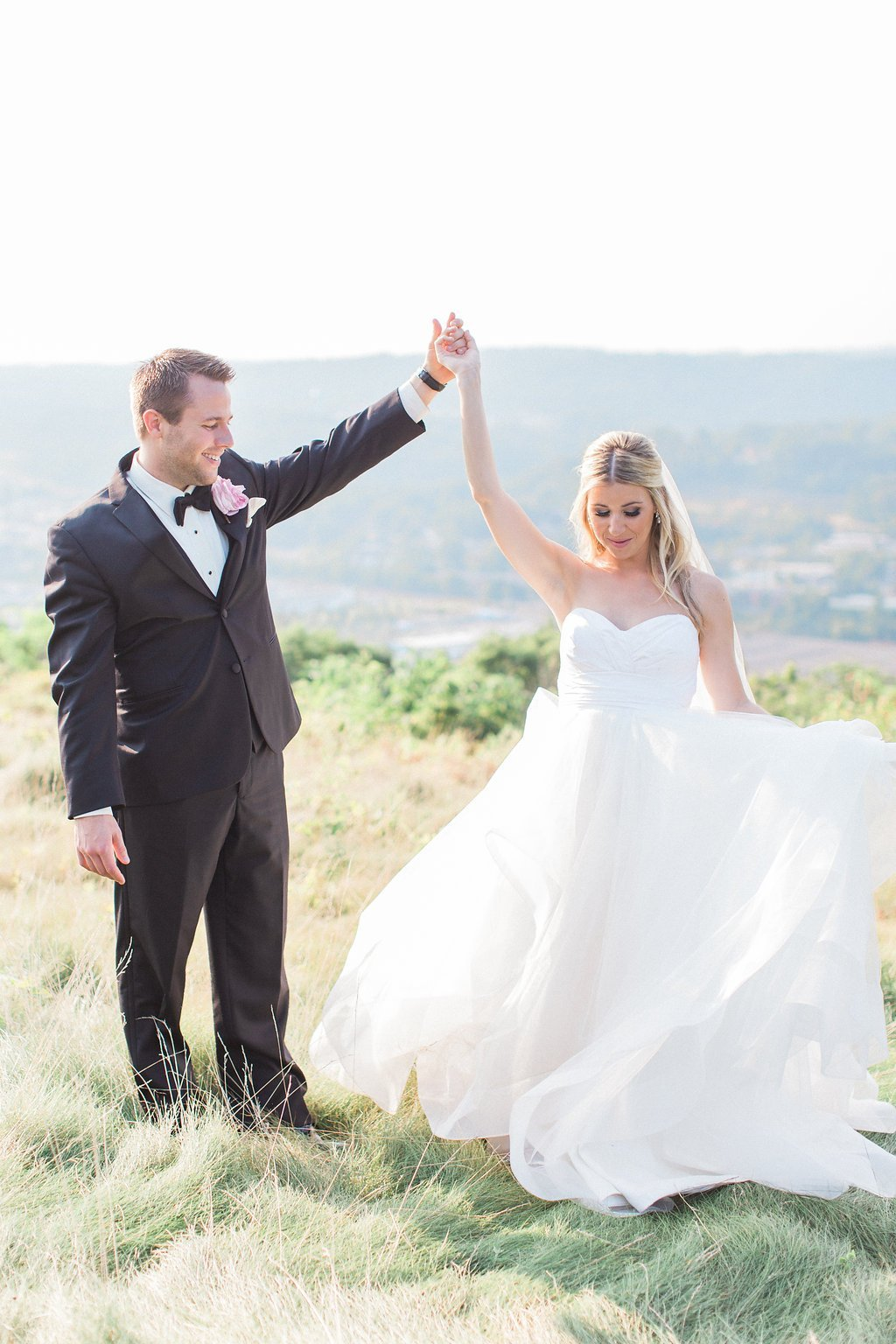Bride and groom dancing together in a field