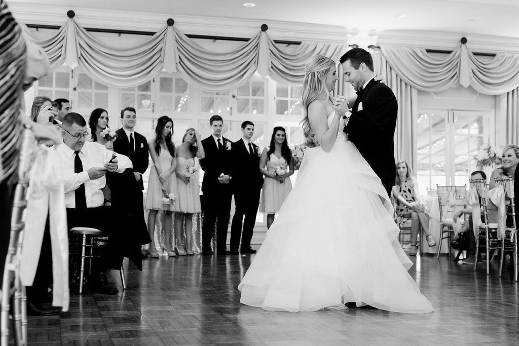bride and groom having their first dance in a black and white photo