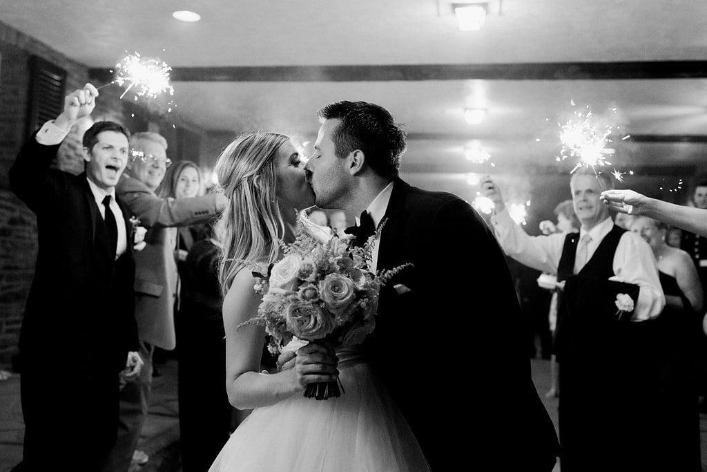 Bride and groom kissing during sparkler send off