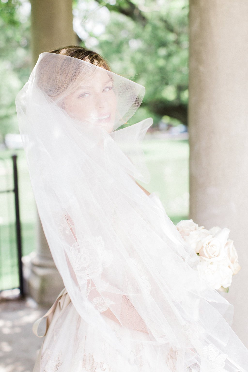 Bride's veil blowing in the wind across her face