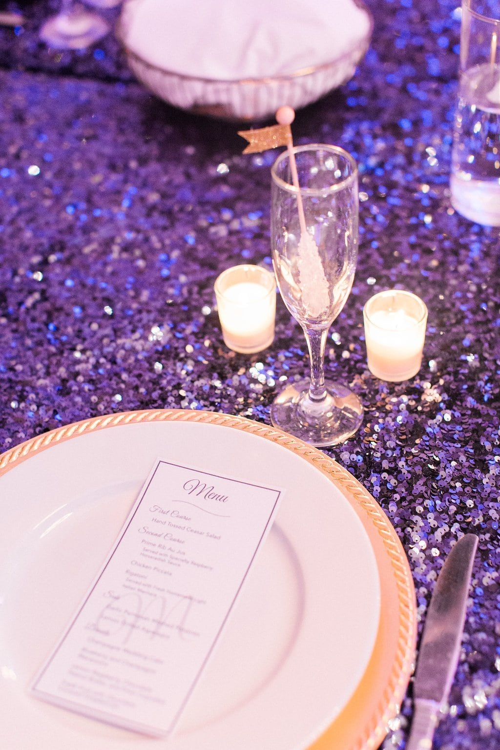 Table setting with blue sequence table cloth and gold plates