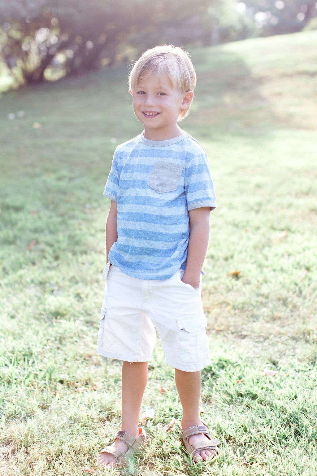 little boy wearing blue striped shirt and white shorts