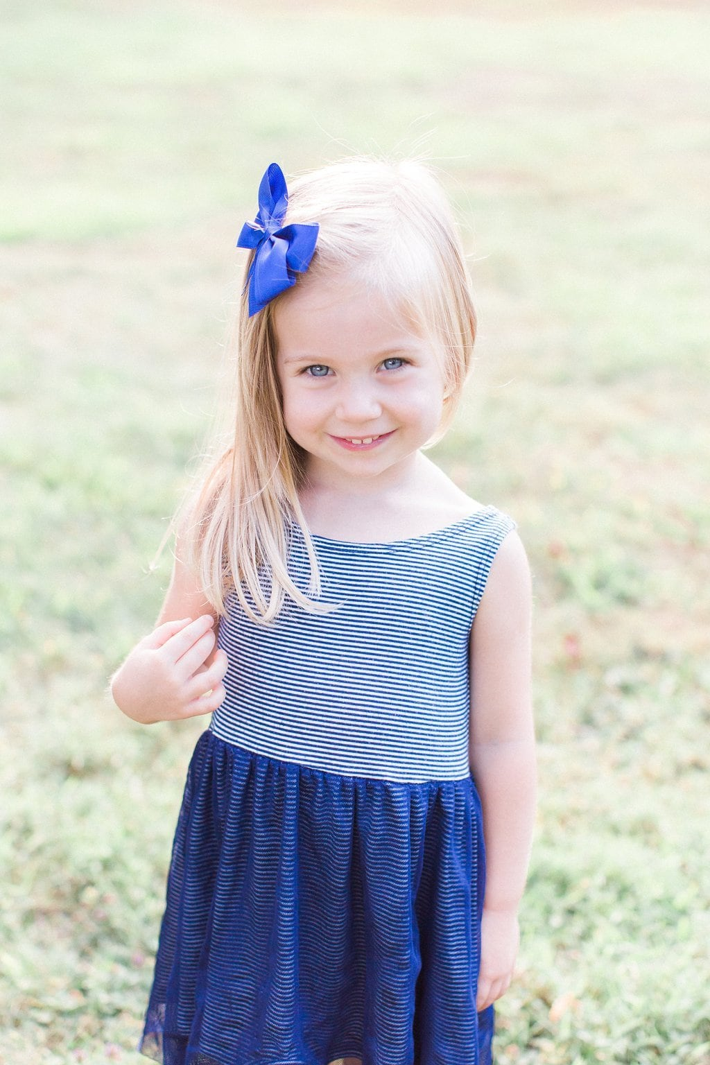 Little girl wearing blue bow and blue striped dress