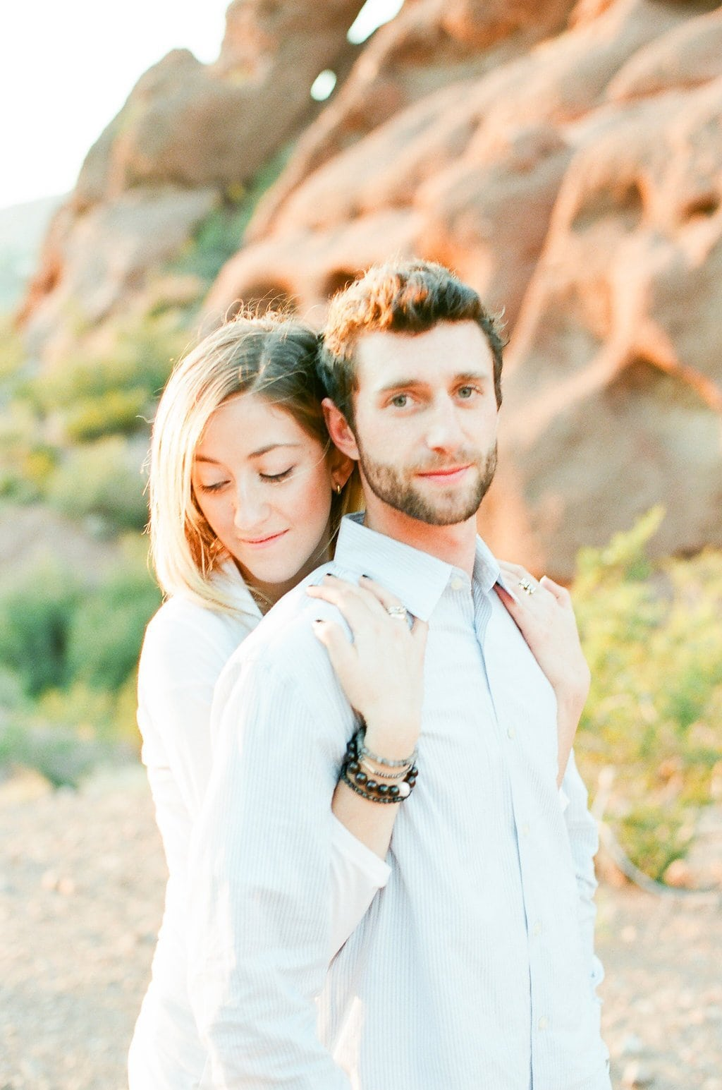 woman embracing man from behind grabbing his shoulders during engagement photos