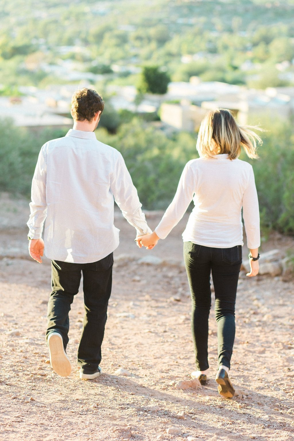 Couple holding hands and walking together down the mountainside