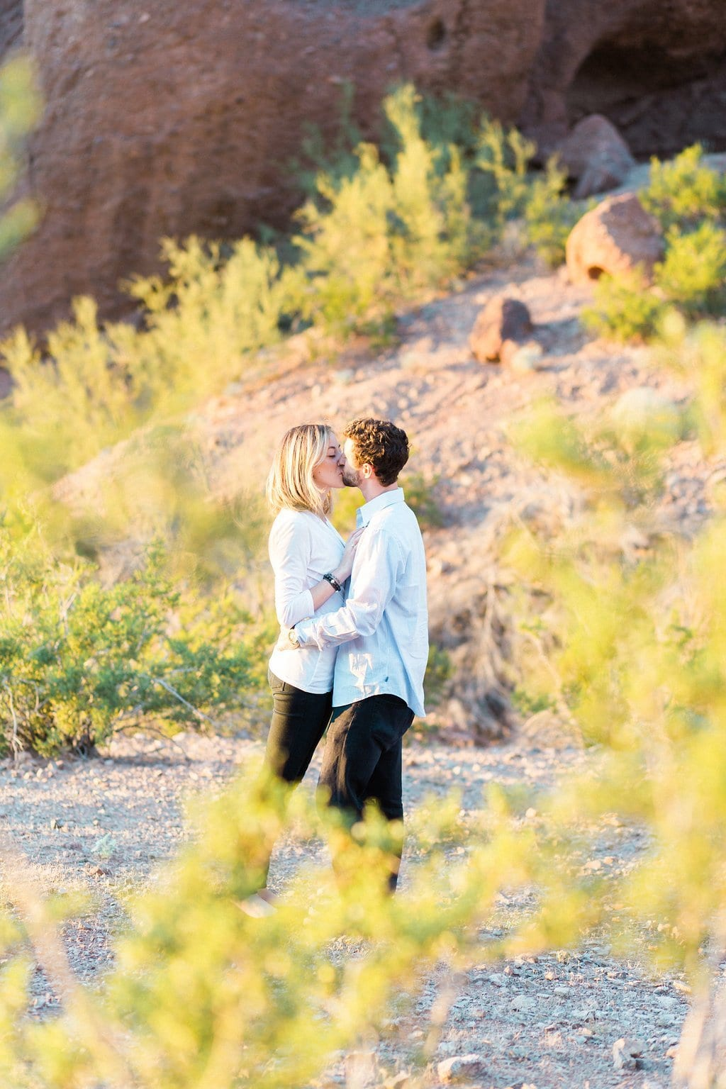 couple kissing in the dessert at sunset