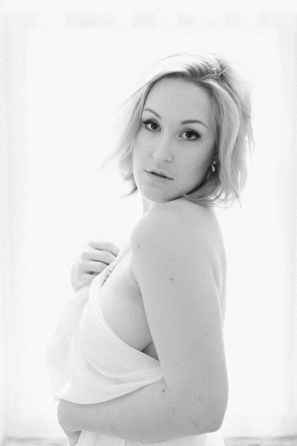 Woman posing naked with a sheet covering her looking over her shoulder