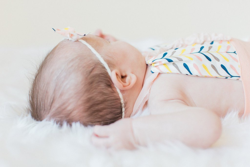 close up of the back of a newborn's head with a pink bow
