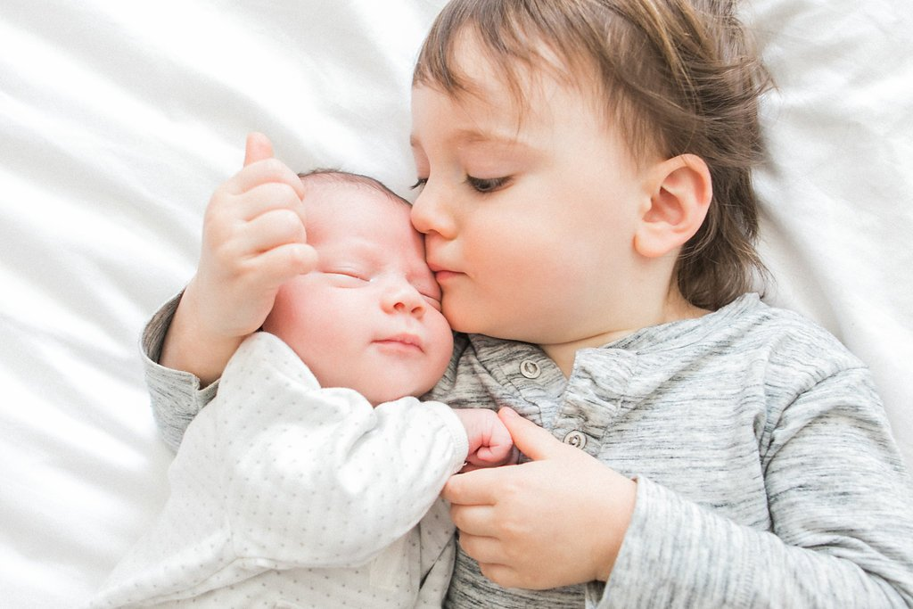 Big brother kissing and embracing baby brother