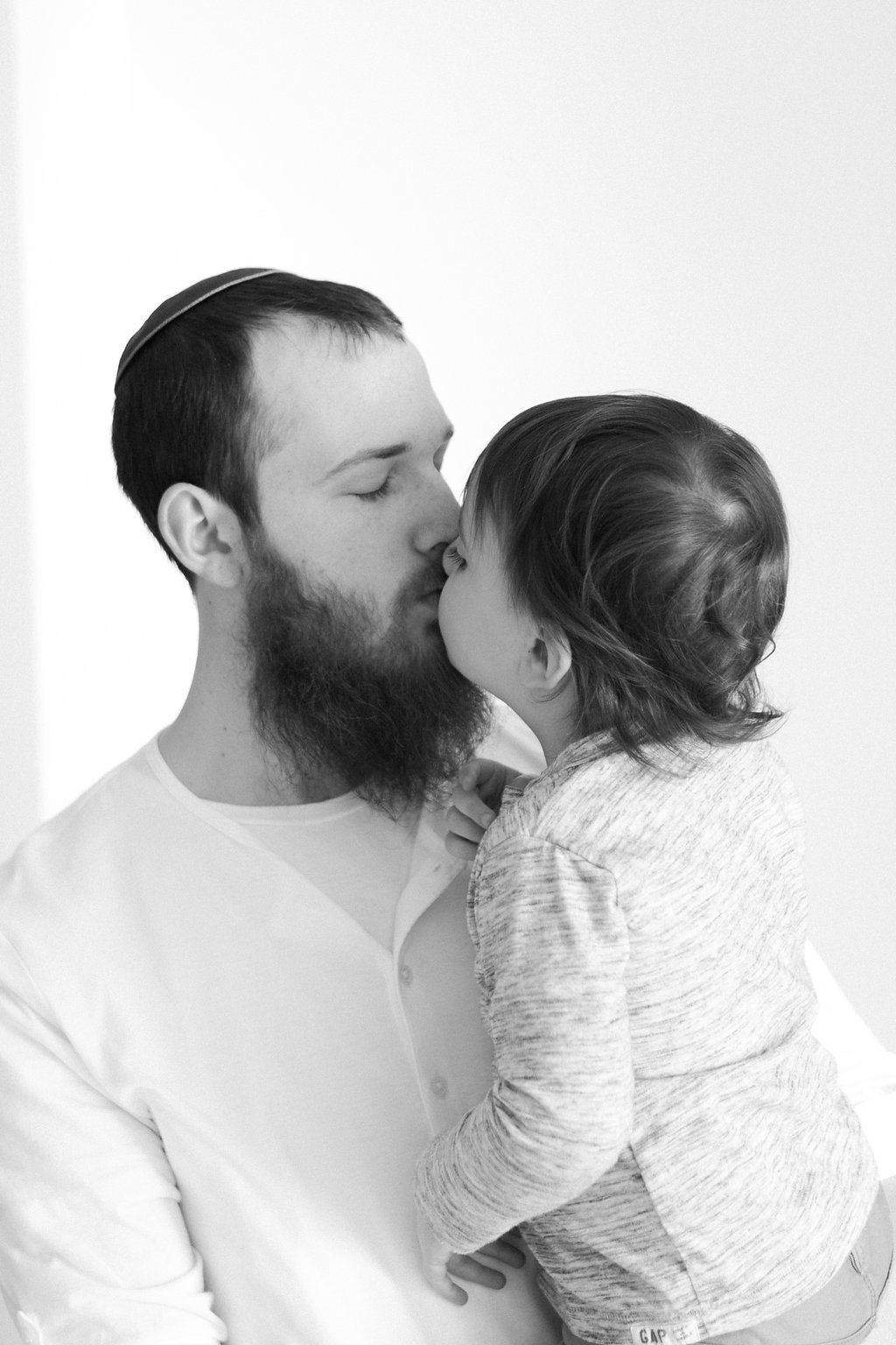 Dad kissing his older son while he jumps on the bed in black and white photo