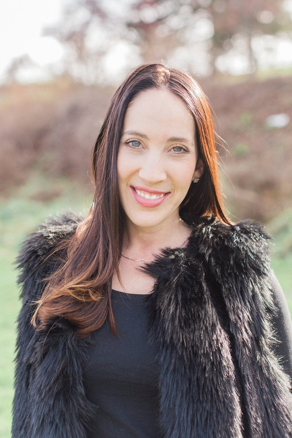 Woman posing for a photograph wearing a black fur vest
