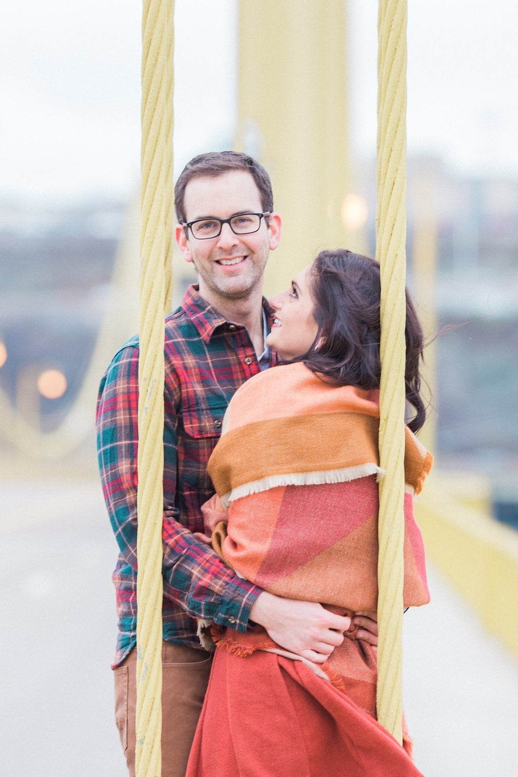 Couple standing on a Pittsburgh bridge dressed in fall clothes