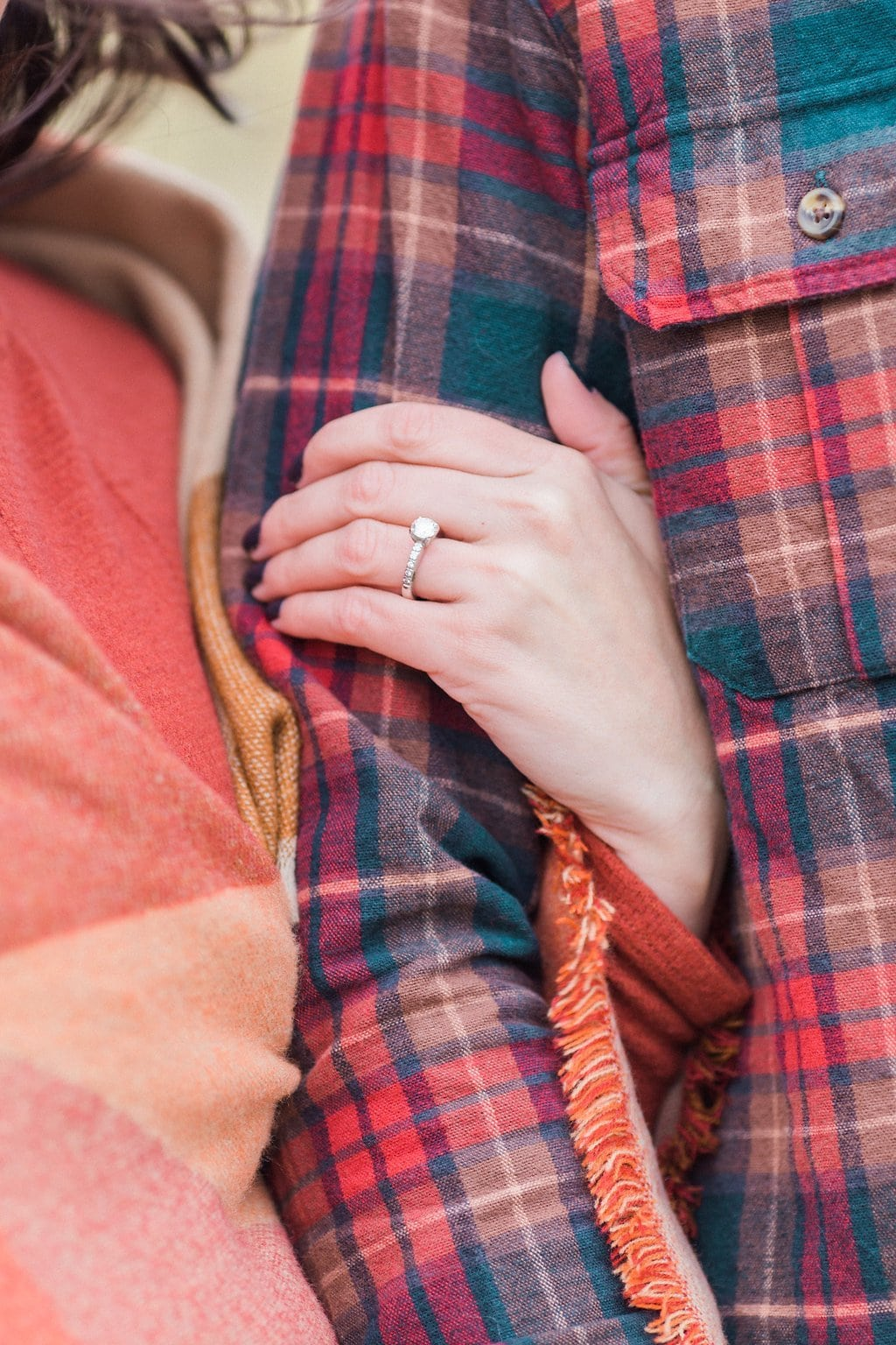 Woman holding man's arm showing off her engagement ring