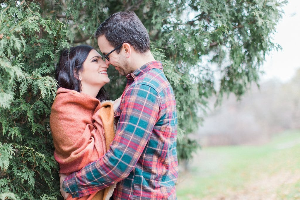 couple posing near evergreen bushes