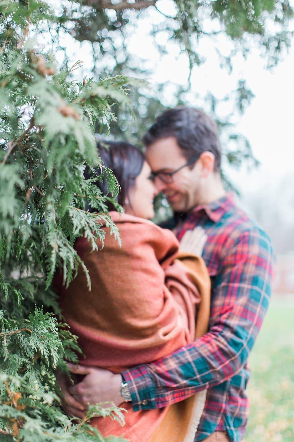 Couple snuggling near evergreen bushes