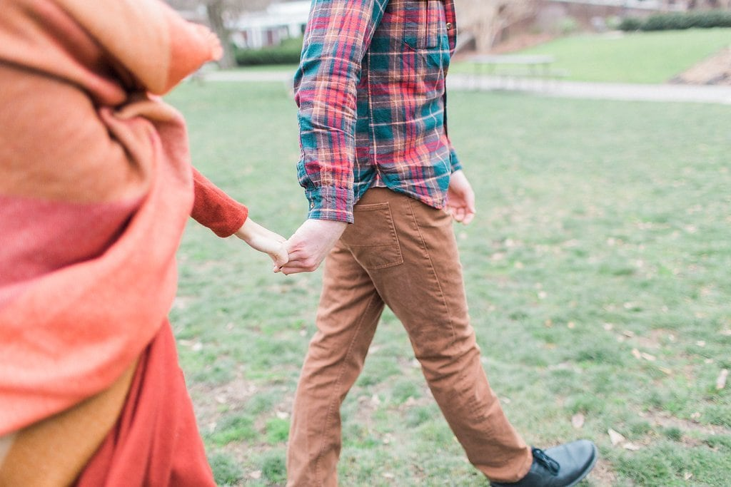 couple holding hands while walking through a field in Pittsburgh's South Side and Mellon Park