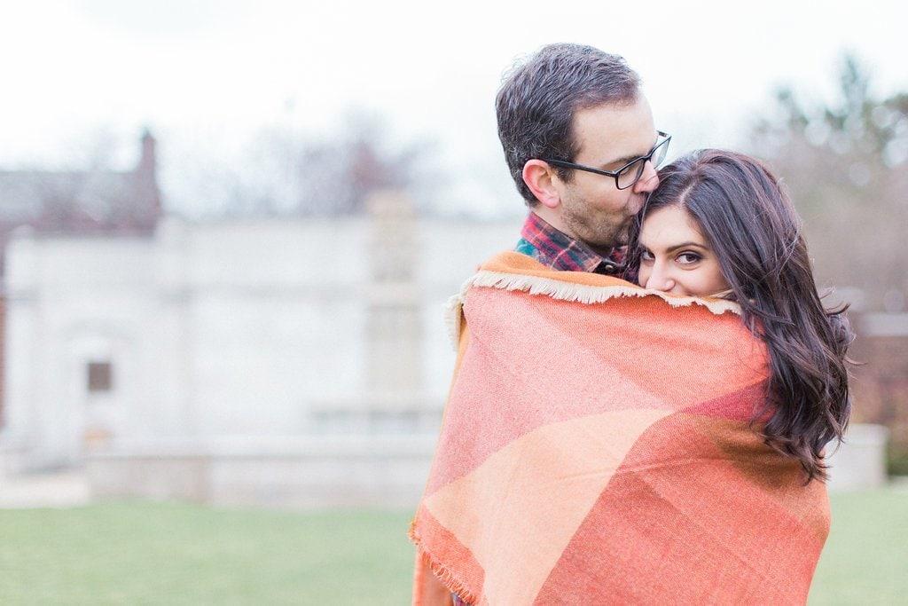 Man and woman cuddling under a plaid blanket