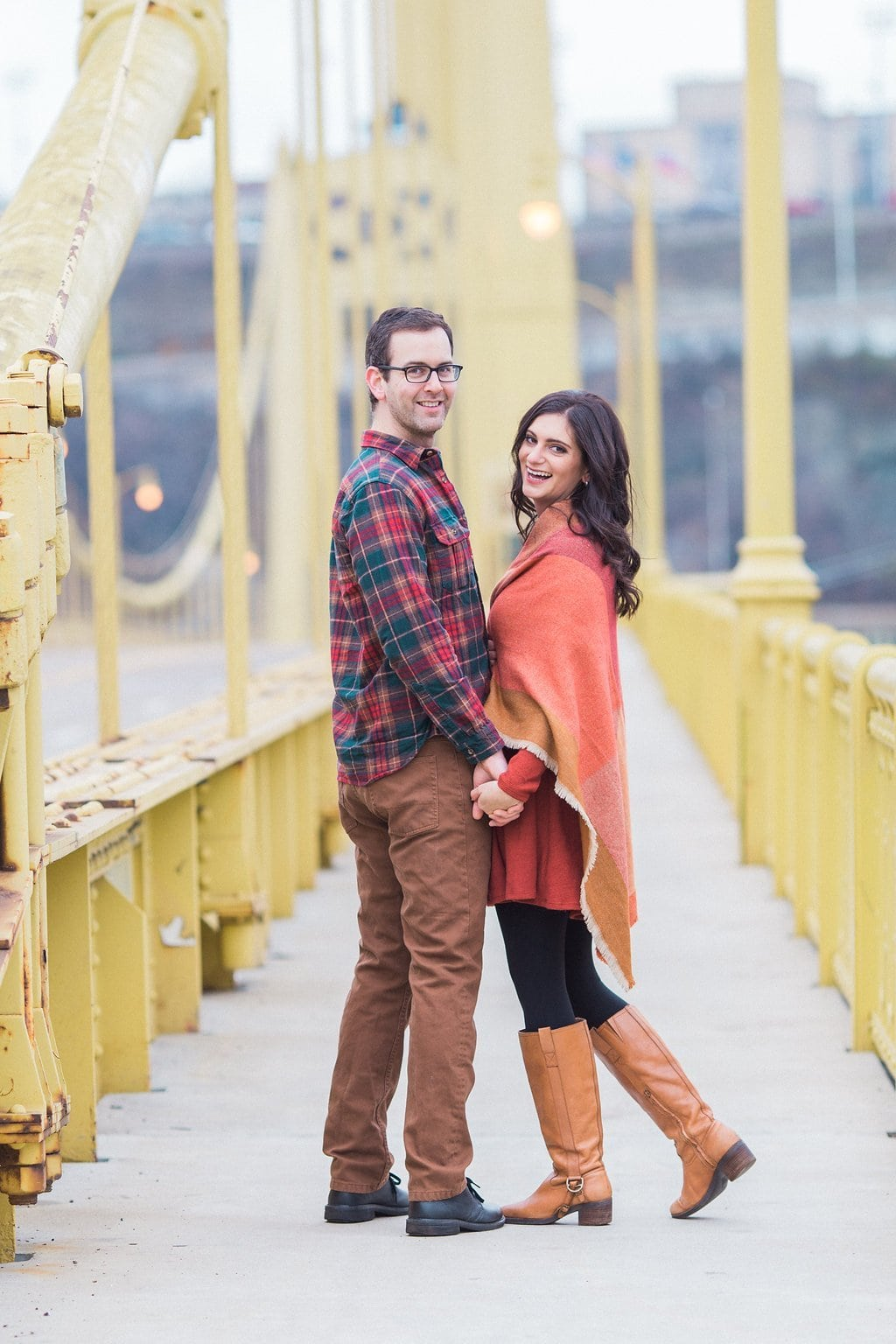 Couple standing on a Pittsburgh bridge holding hands and wearing fall clothes