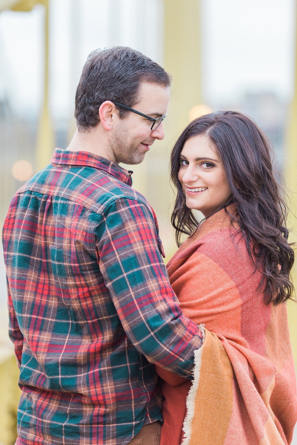 Woman looking back over her shoulder posing with fiance in fall clothes