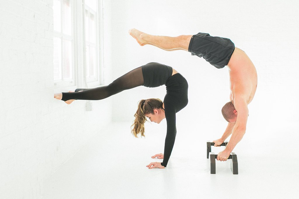 Man and woman holding bridge pose without feet touching the ground