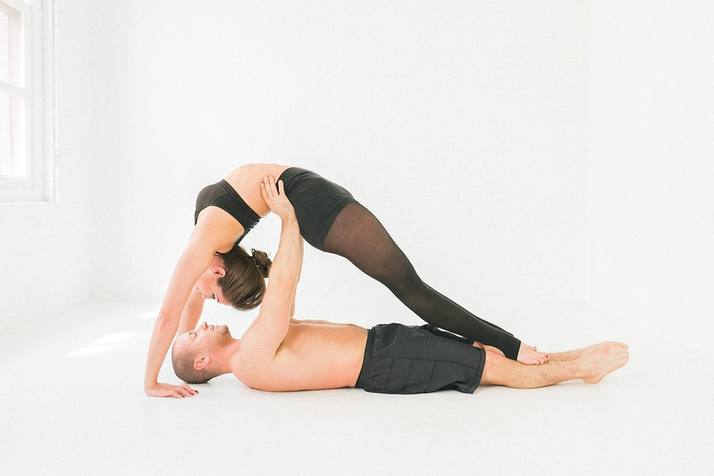 Man laying on the ground under a woman who is doing a backbend over him with straight legs