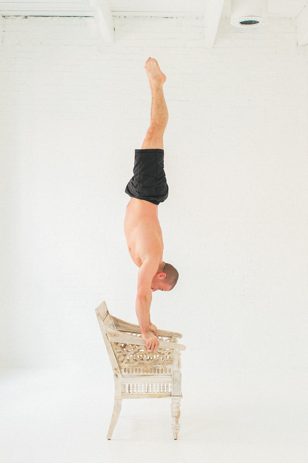 Man holding a handstand on a chair