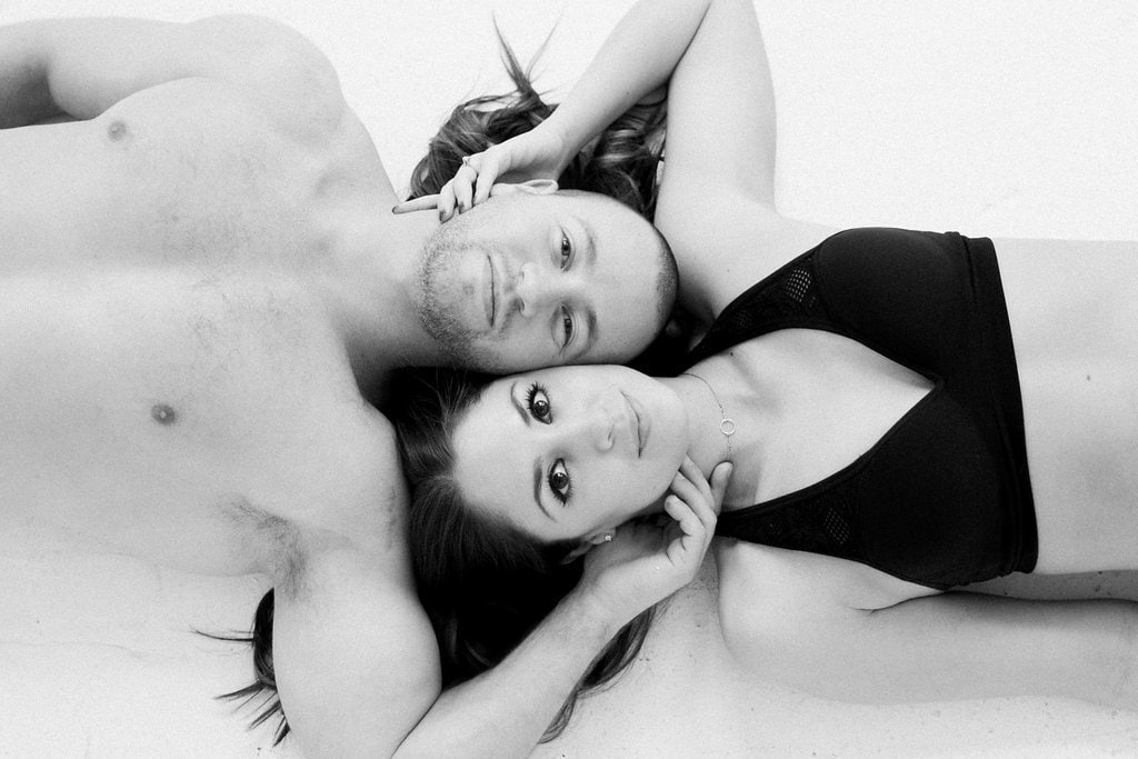 Overhead photo of man and woman laying on the ground together in black and white