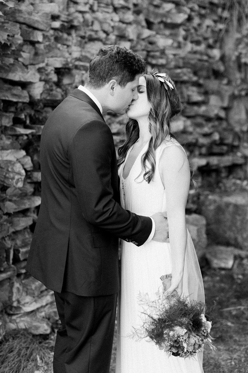 Black and white photo of the bride and groom kissing after their first look