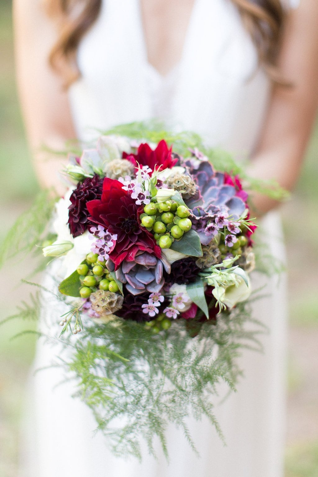 Bride holding purple, red, and burgundy colors bouquet