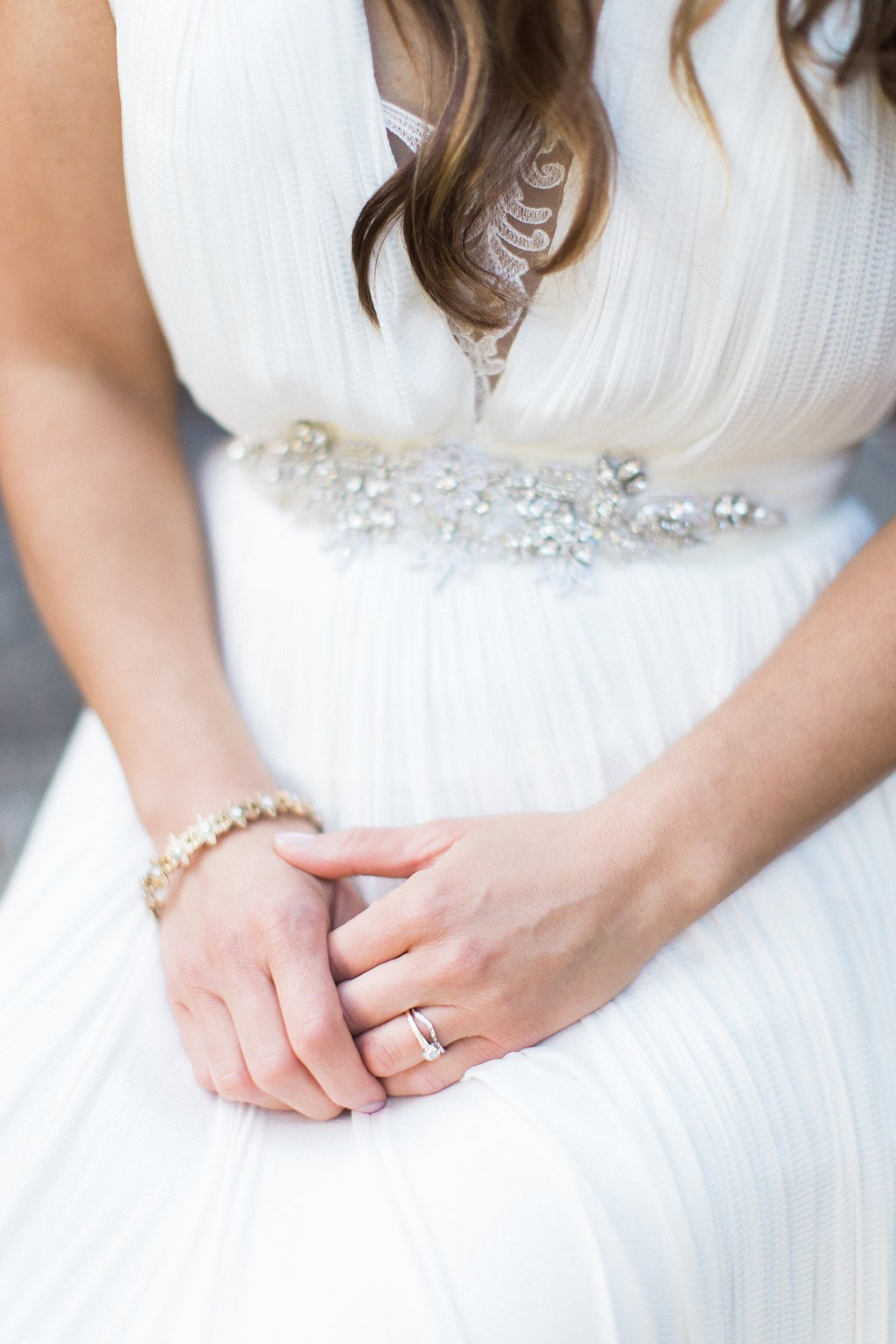 Close up of bride's hands resting on her lap showing her engagement ring