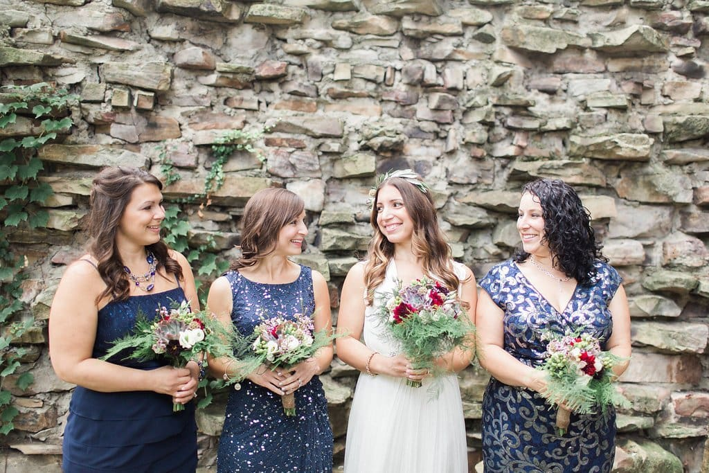 Bridesmaids wearing blue dresses standing with purple bouquets and the bride