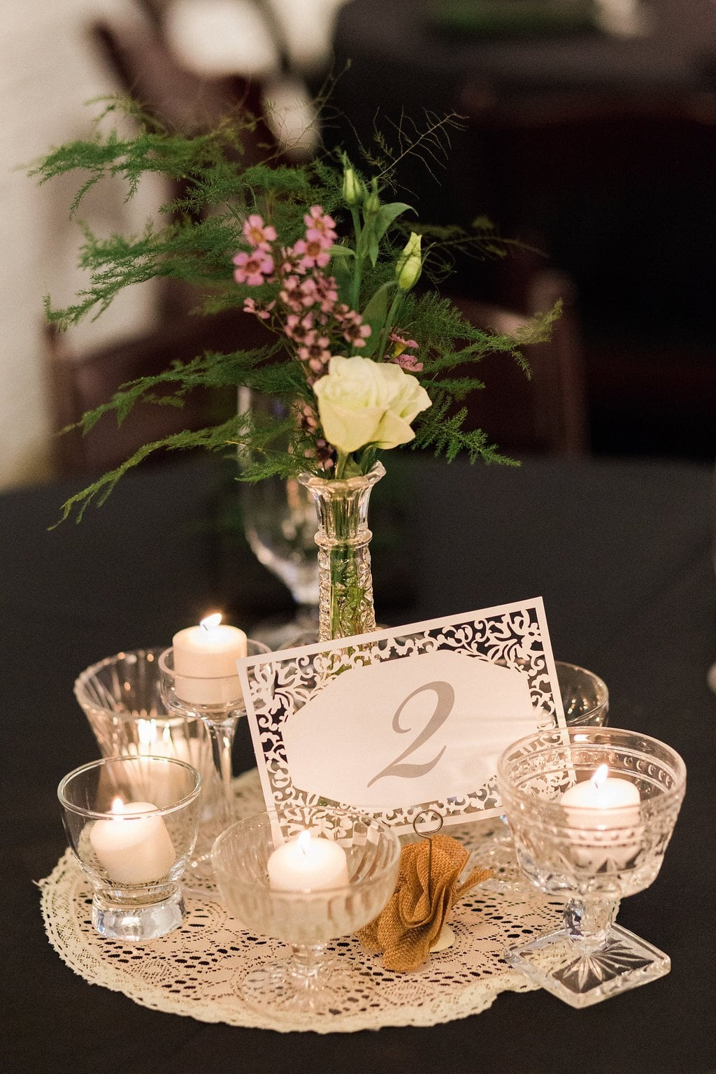 White paper cut table numbers with lace and candle decor