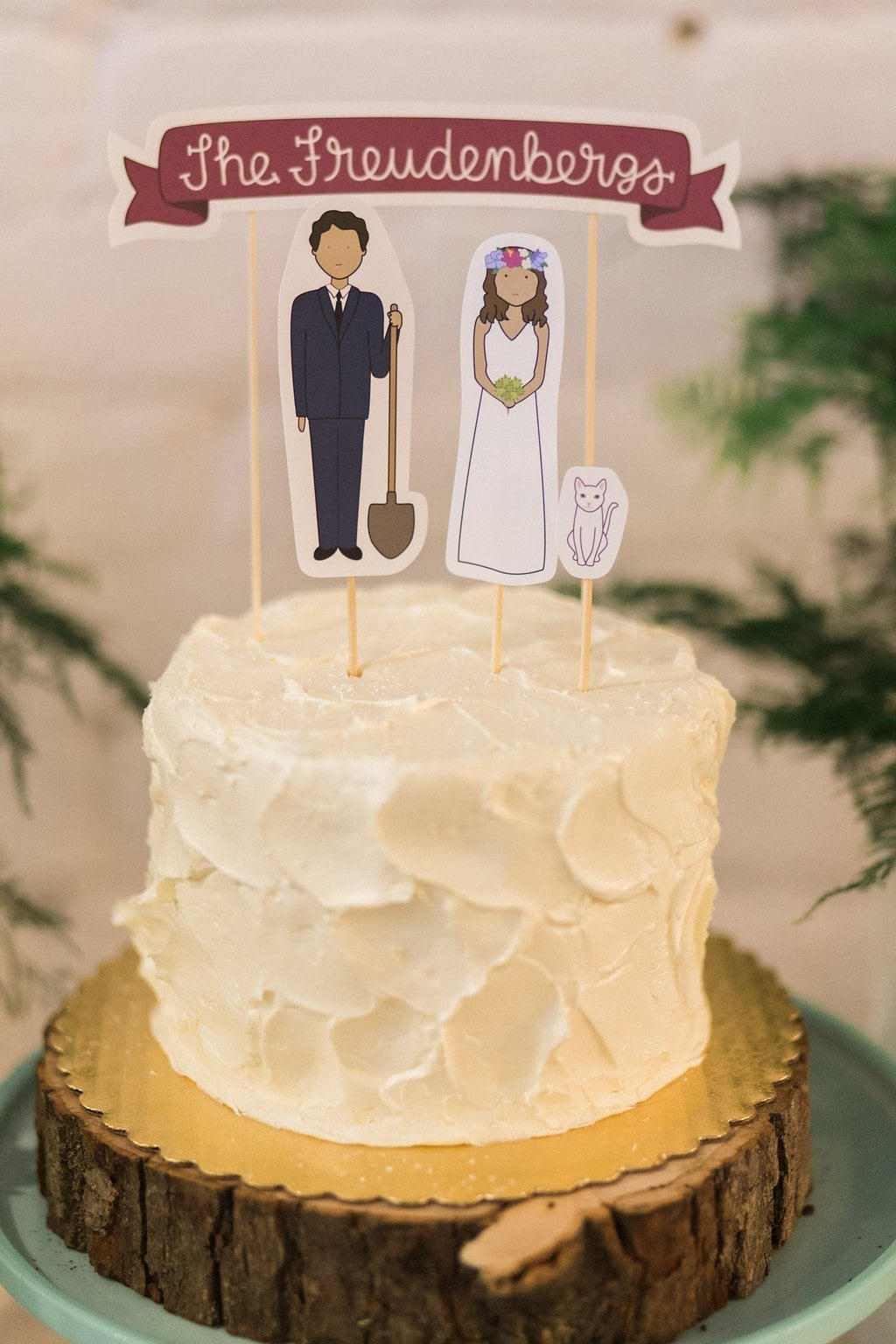 Small white cake with paper bride and groom toppers